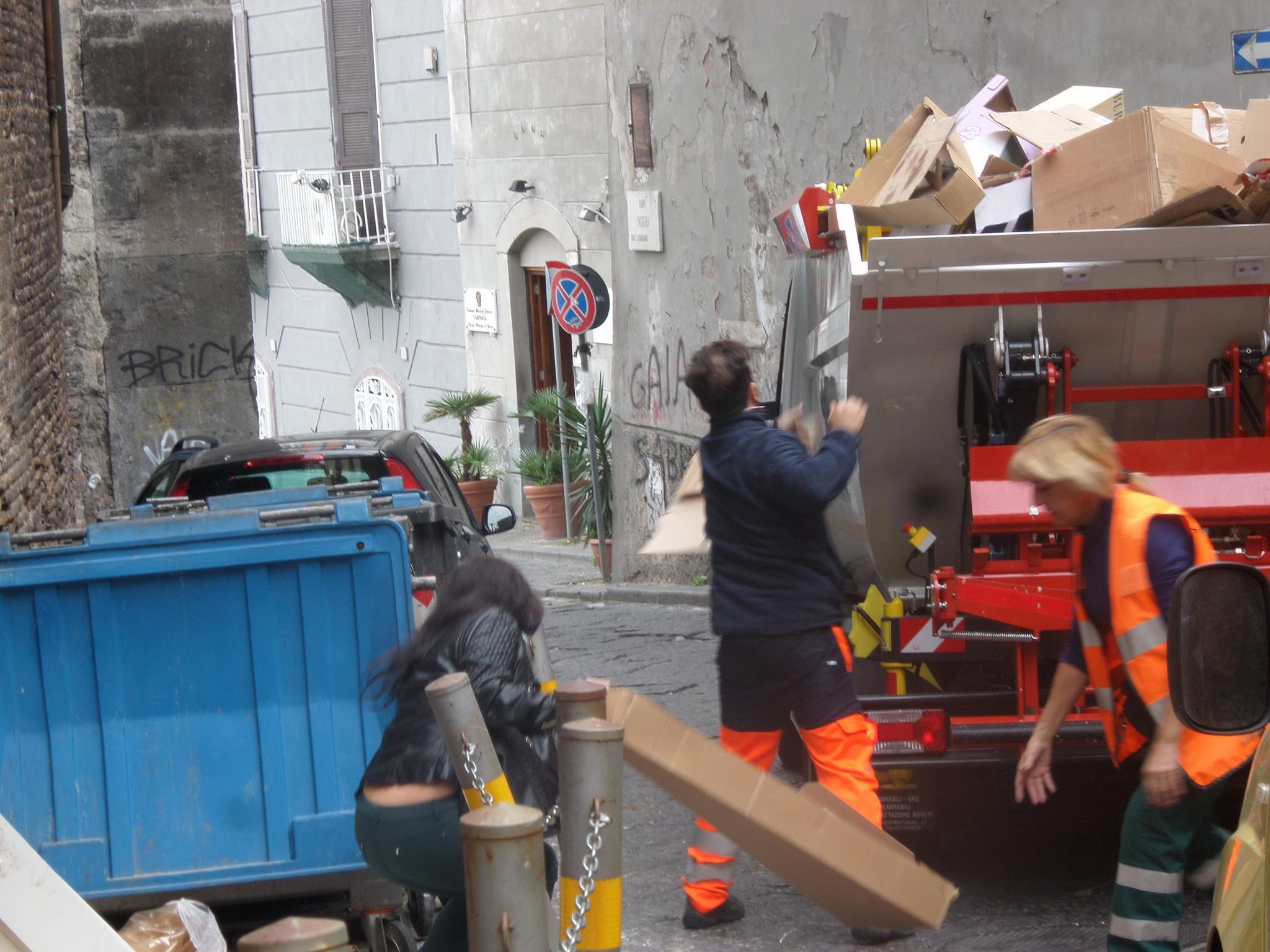 cittadini aiutano gli operatori dell'Asia a prelevare i rifiuti